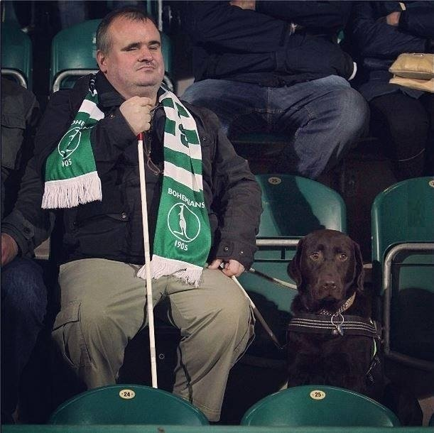 True dedication. That dog looks so confused as to why they are at the game... Look at the guy's face, he's feeling it.